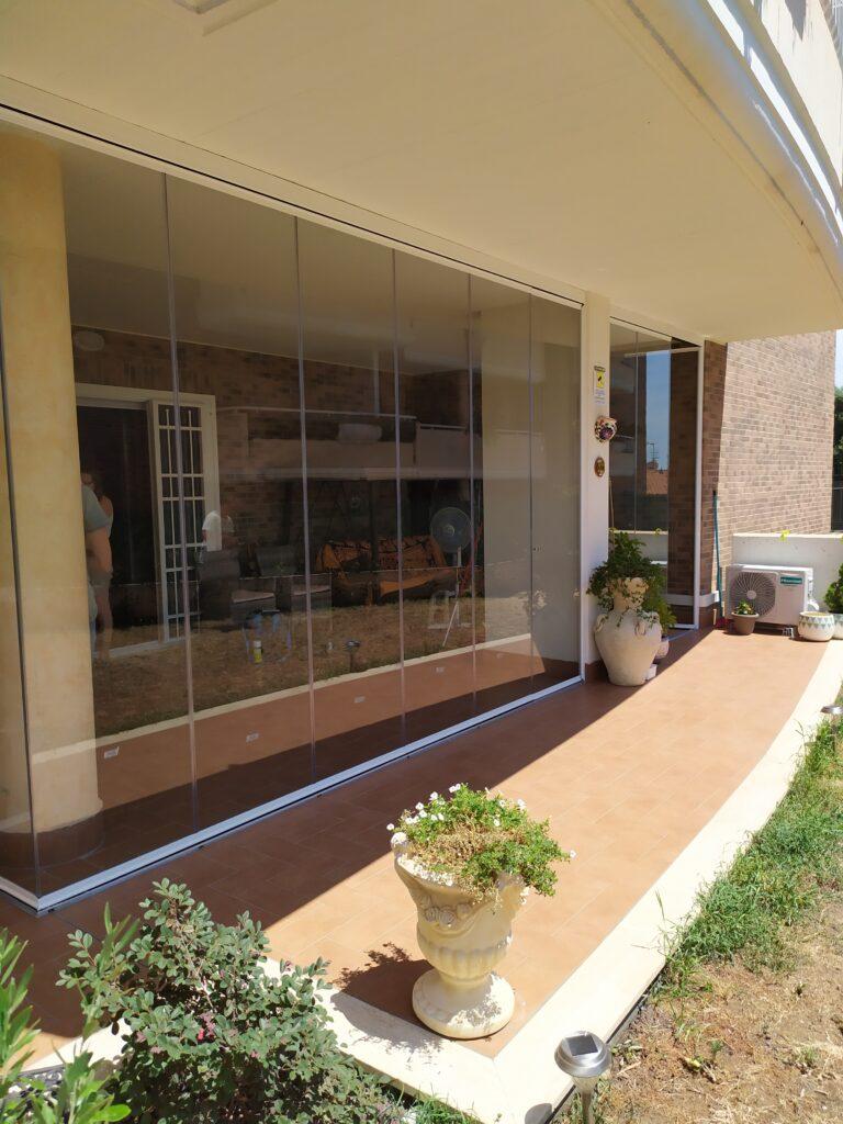Portico con chiusura vetrata panoramica con porta